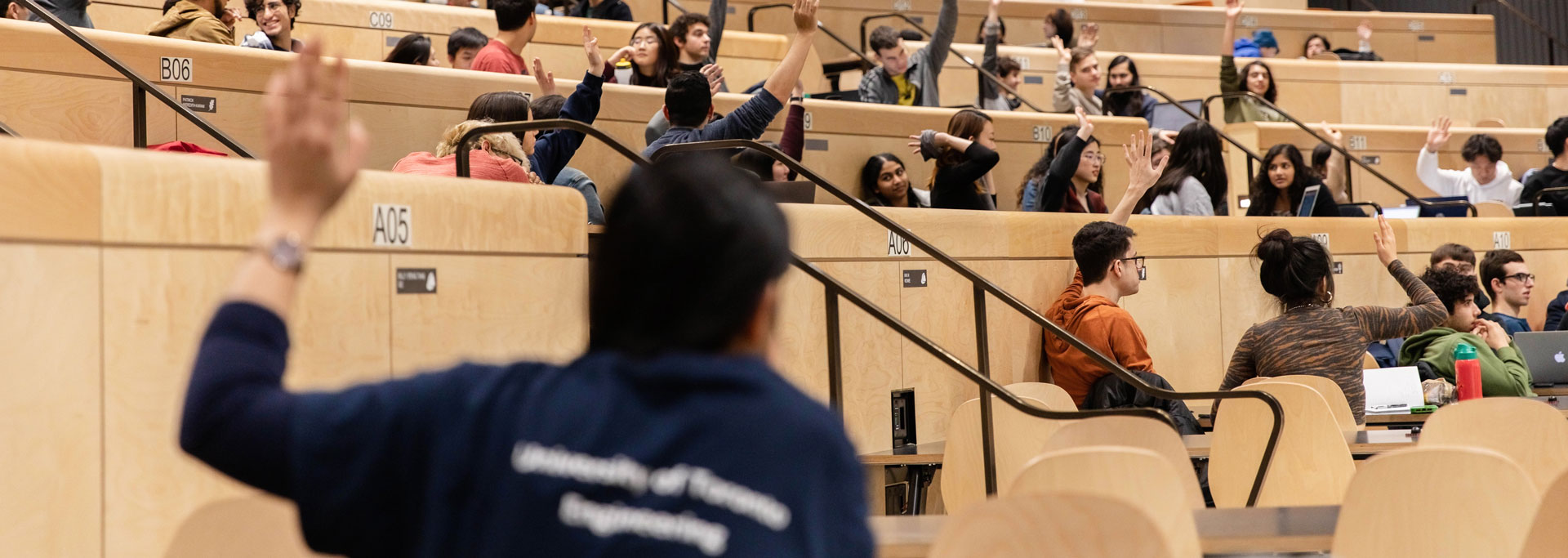 students with hands raised in a class